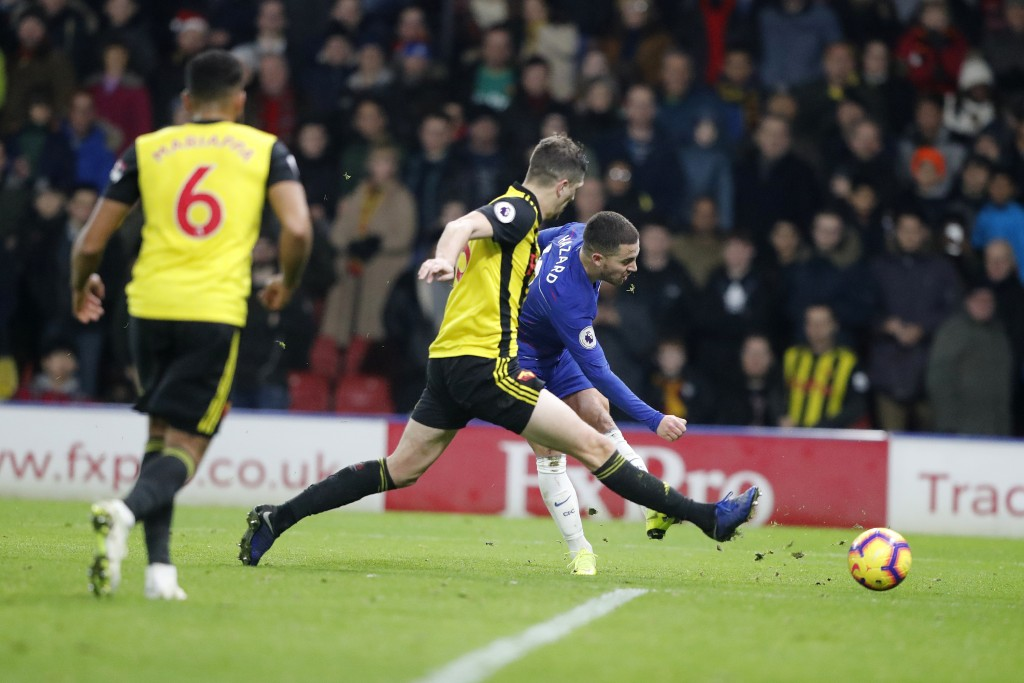 Chelsea's Eden Hazard, back shots the ball past Watford's Craig Cathcart, center during the English Premier League soccer match between Watford and Ch...