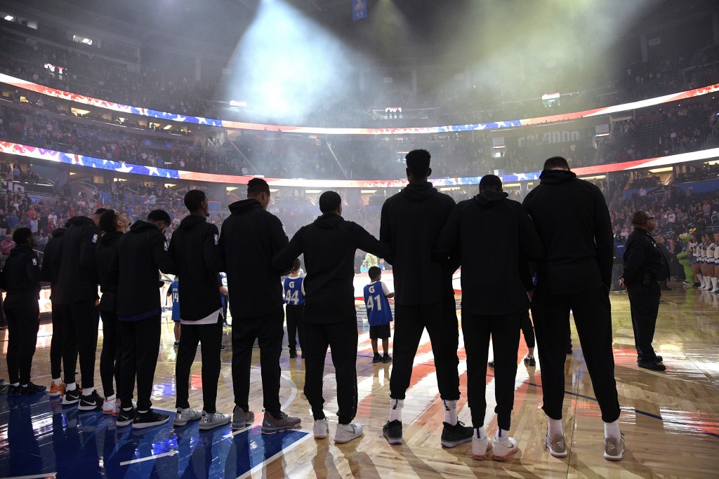 Phoenix Suns players lock arms during the singing of the national anthem before an NBA basketball game against the Orlando Magic on Wednesday, Dec. 26...