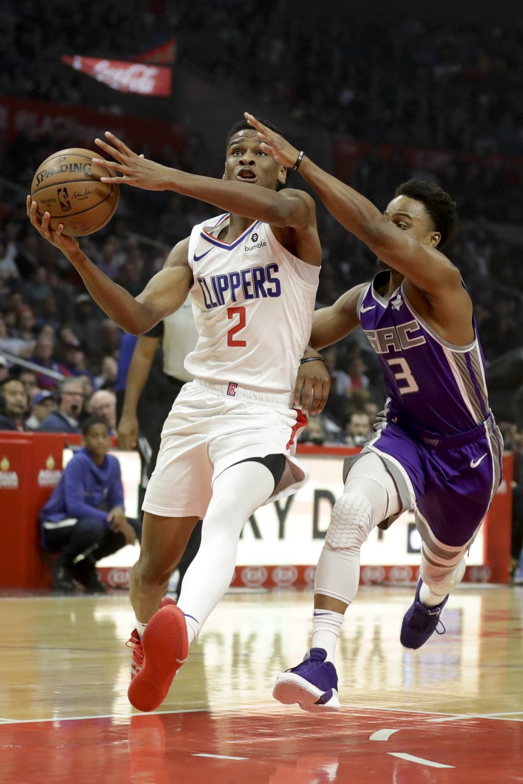Los Angeles Clippers guard Shai Gilgeous-Alexander, left, drives to the basket around Sacramento Kings guard Yogi Ferrell during the first half of an ...
