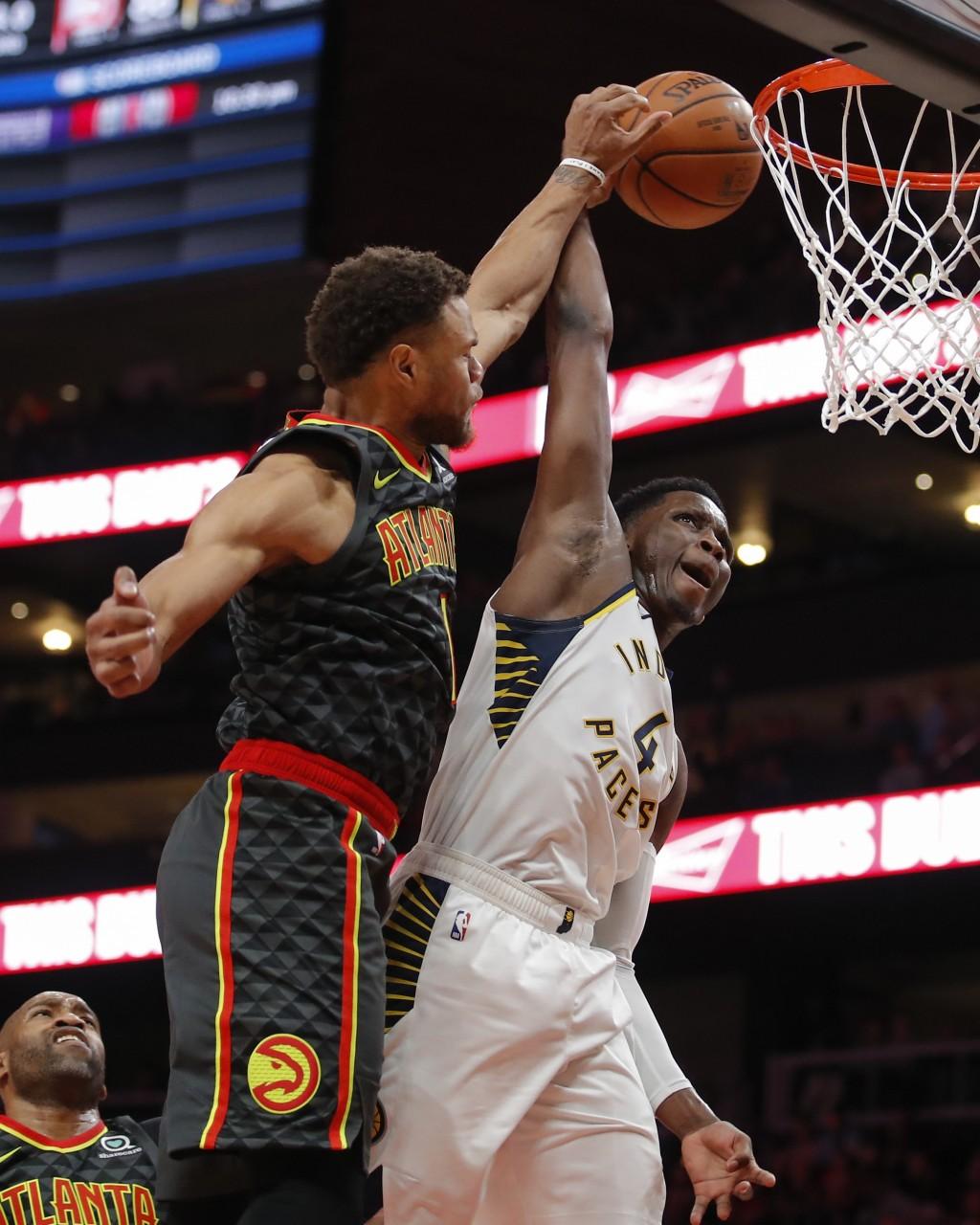 Indiana Pacers guard Victor Oladipo (4) has his shot deflected by Atlanta Hawks guard Justin Anderson (1) during the second half of an NBA basketball ...