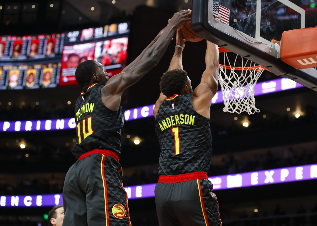 Atlanta Hawks guard Justin Anderson (1) and center Dewayne Dedmon (14) go up for the double jam in the first half of an NBA basketball game against th...