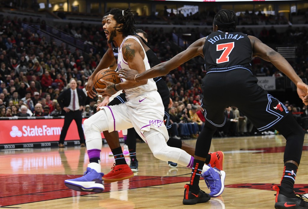 Minnesota Timberwolves guard Derrick Rose (25) drives to the basket past Chicago Bulls forward Justin Holiday (7) during the first half of an NBA bask...
