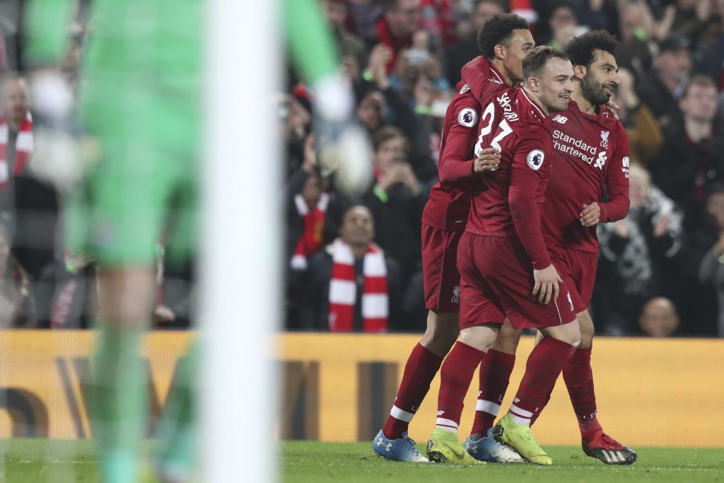 Liverpool's Xherdan Shaqiri, center, celebrates with teammates Mohamed Salah, right, after scoring his side's third goal during the English Premier Le...