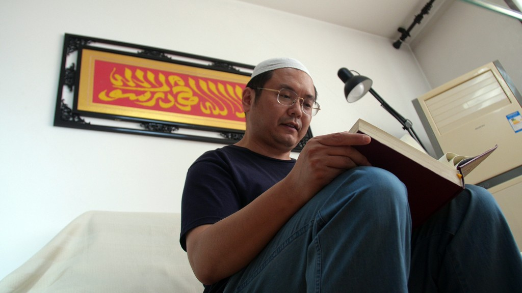 In this Sept. 28, 2018 photo, Muslim Chinese poet Cui Haoxin reads an Arabic prayer from a Quran in his home underneath a tapestry woven by his mother