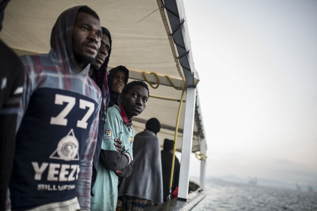 Migrants look out from the deck of the Spanish NGO Proactiva Open Arms rescue vessel, after being rescued Dec. 21, in the Central Mediterranean Sea, b...