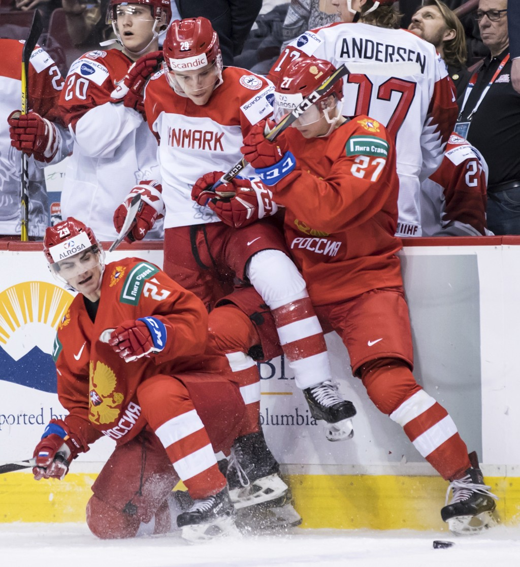 Denmark's Victor Cubars, center, battles Russia's Kirill Slepets, left, and Mark Rubinchik, right, for the puck during the second period of a world ju