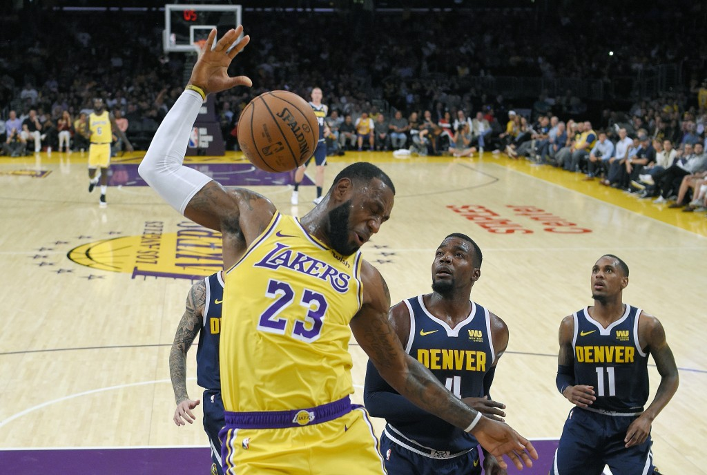 FILE - In this Tuesday, Oct. 2, 2018, file photo, Los Angeles Lakers forward LeBron James, left, follows through on a dunk as Denver Nuggets forward P...