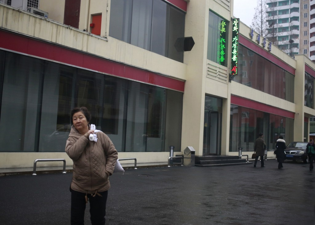 """In this Dec. 21, 2018, photo, a North Korean woman walks outside Bugsae Shop, also known as the """"Singapore Shop,"""" in Pyongyang, North Korea. Despite t"""