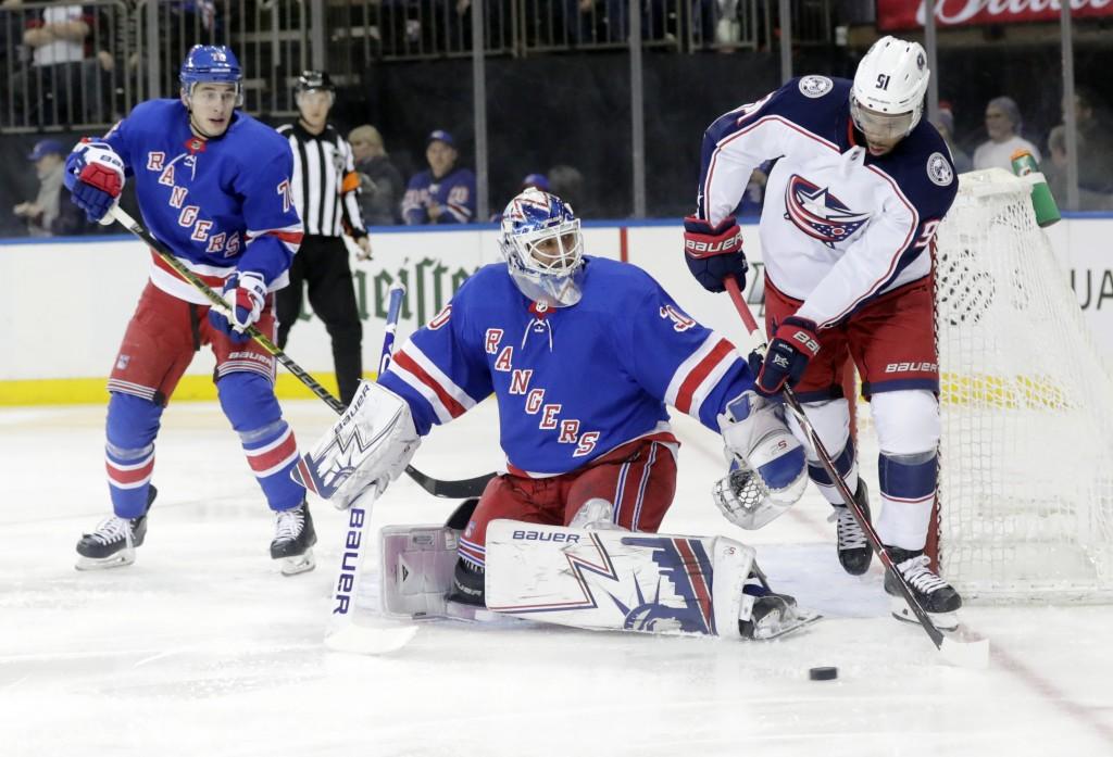 New York Rangers goaltender Henrik Lundqvist, center, watches Columbus Blue Jackets' Anthony Duclair (91) skate behind him during the first period of ...
