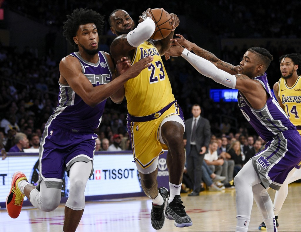 FILE - In this Oct. 4, 2018, file photo, Los Angeles Lakers forward LeBron James, center, drives between Sacramento Kings forward Marvin Bagley III, l...