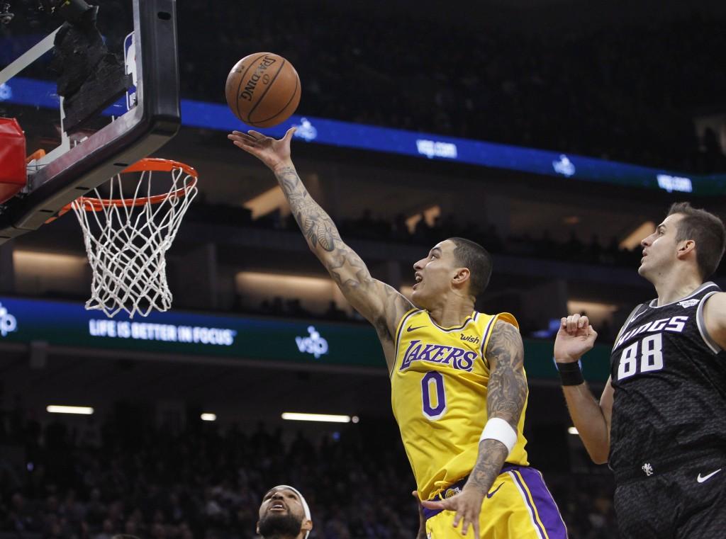 Los Angeles Lakers forward Kyle Kuzma (0) shoots next to Sacramento Kings forward Nemanja Bjelica (88) during the first half of an NBA basketball game...
