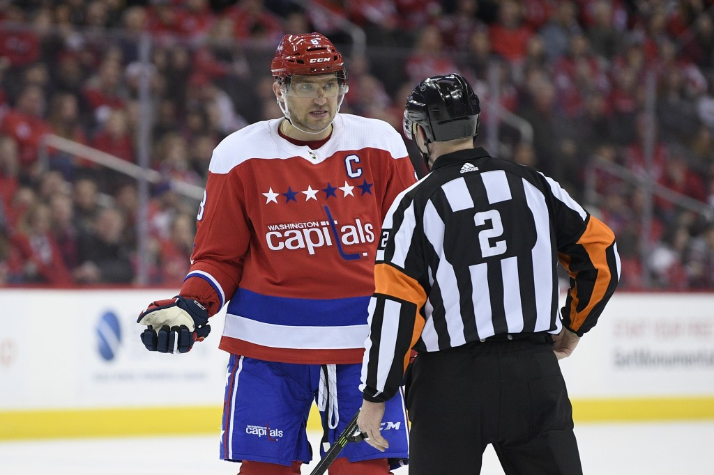 Washington Capitals left wing Alex Ovechkin (8), of Russia, talks with referee Jon McIsaac (2) during the first period of an NHL hockey game against t...