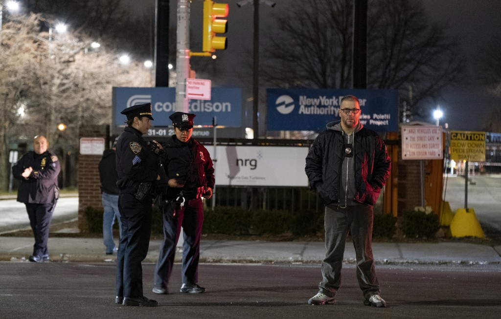 Law enforcement personnel stand in front of a Con Edison facility in the Queens borough of New York, Thursday, Dec. 27, 2018, where an earlier transfo...
