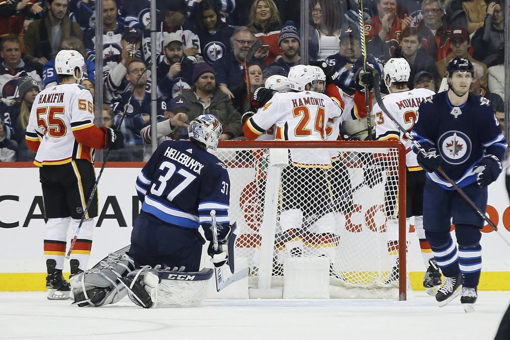 Calgary Flames celebrate Johnny Gaudreau's (13) second goal against Winnipeg Jets goaltender Connor Hellebuyck (37) during second-period NHL hockey ga...