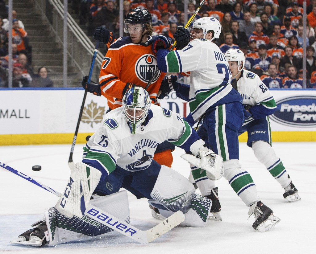 Vancouver Canucks goalie Jacob Markstrom (25) turns the puck away as Edmonton Oilers' Connor McDavid (97) and Canucks' Ben Hutton (27) work in front o...