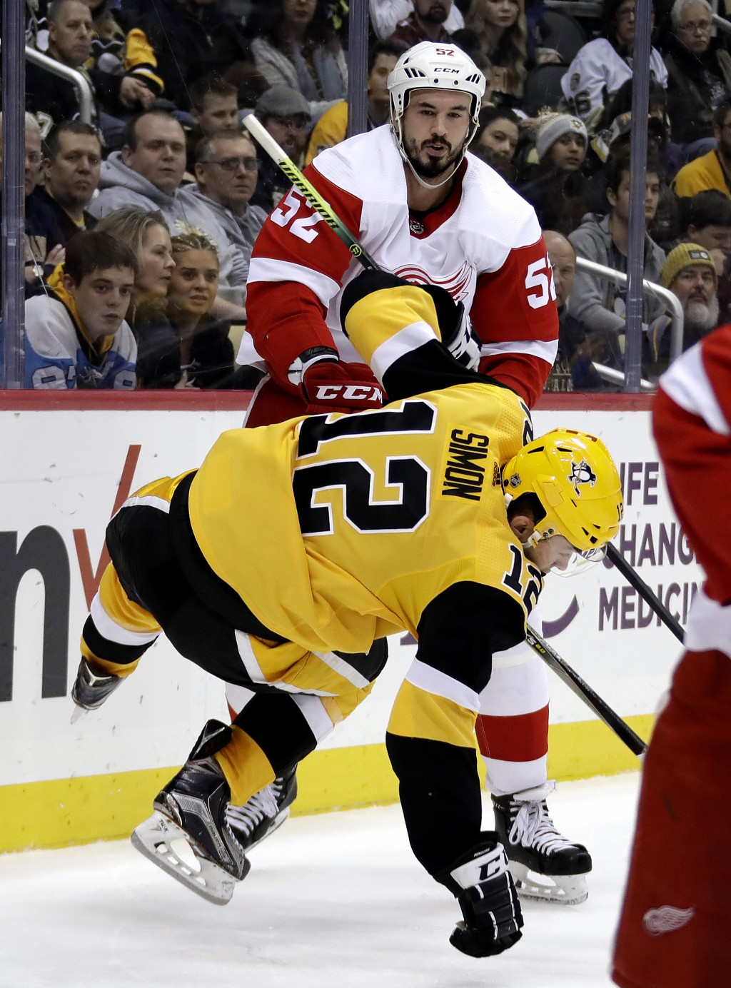 Pittsburgh Penguins' Dominik Simon (12) is hit by Detroit Red Wings' Jonathan Ericsson (52) during the second period of an NHL hockey game in Pittsbur