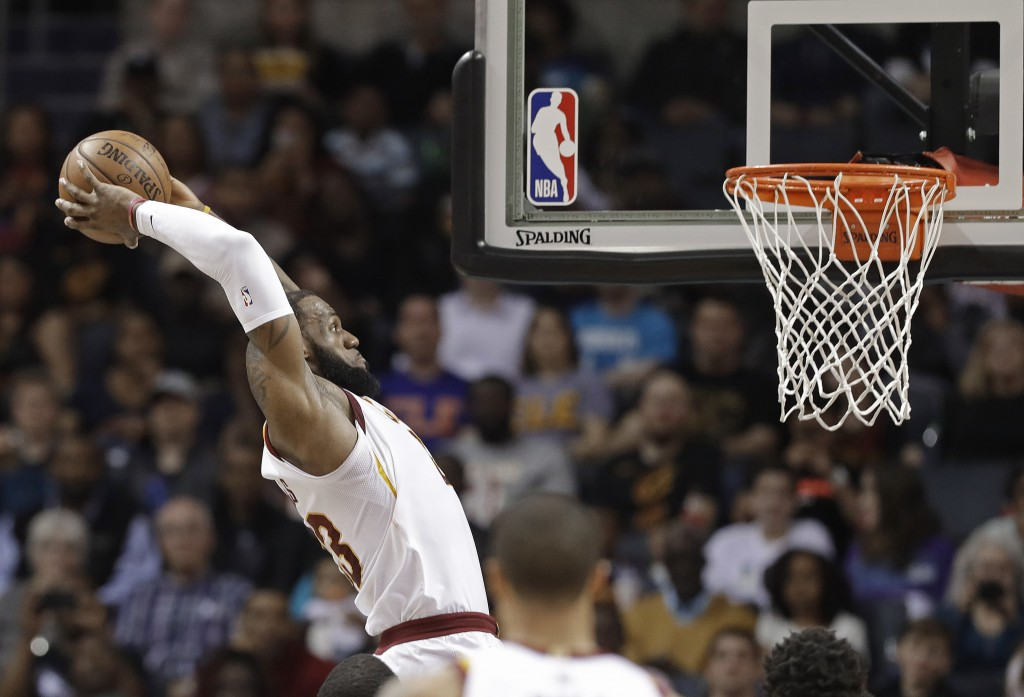 FILE - In this March 28, 2018, file photo, Cleveland Cavaliers' LeBron James goes up to dunk against the Charlotte Hornets during the first half of an...