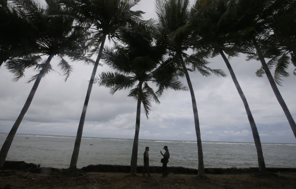 People stand on the shore near the recent tsunami near Carita beach, Indonesia, Friday, Dec. 28, 2018. Indonesia raised the danger level for an island