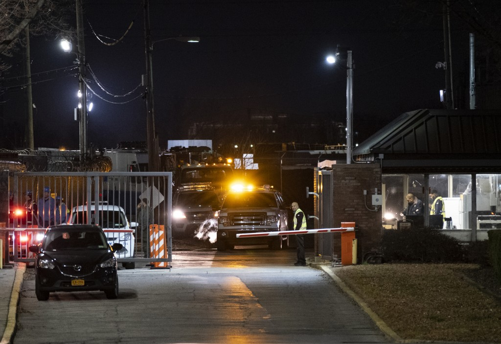 People stand at the gate of a Con Edison facility in the Queens borough of New York, Thursday, Dec. 27, 2018, where an earlier transformer explosion l...