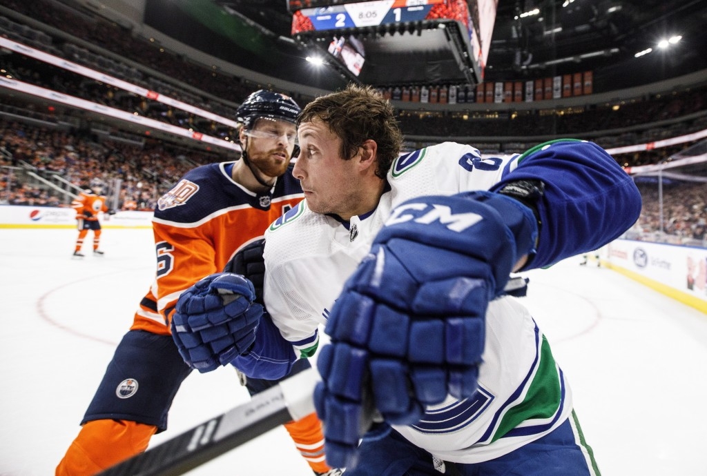 Vancouver Canucks' Jay Beagle (83) and Edmonton Oilers' Adam Larsson (6) compete for the puck during the first period of an NHL hockey game Thursday, ...