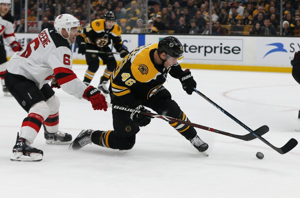 New Jersey Devils defenseman Andy Greene (6) and Boston Bruins center David Krejci (46) reach for the puck during the second period of an NHL hockey g...