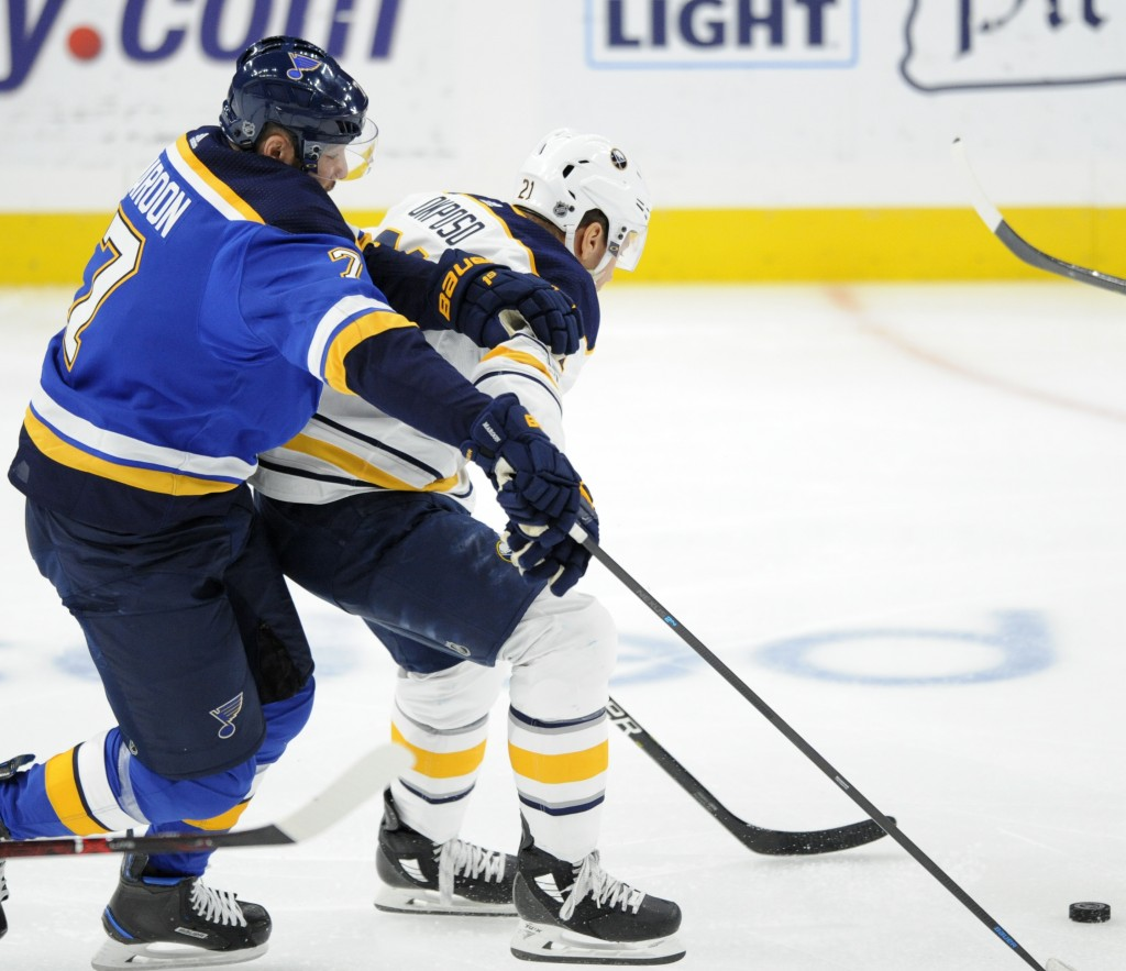 St. Louis Blues' Pat Maroon (7) battles for the puck with Buffalo Sabres' Kyle Okposo (21) during the first period of an NHL hockey game, Thursday, De