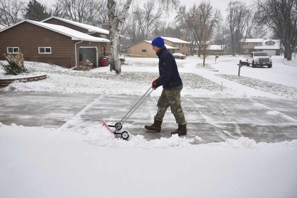 In this Wednesday, Dec. 26, 2018 photo, Lance Nieuwenhuis shovels snow out of his driveway in Sioux Falls, S.D. The weather service in Sioux Falls, So