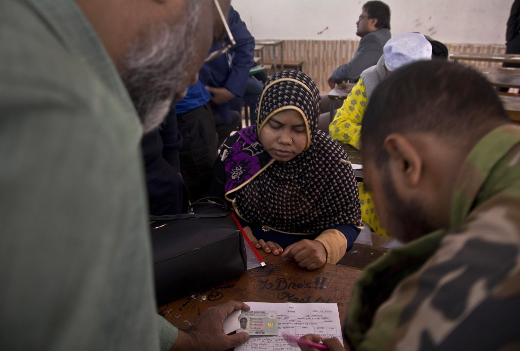 Bangladeshi election officials help a woman to find name of her family member in the voters list at a polling station ahead of the general elections i...