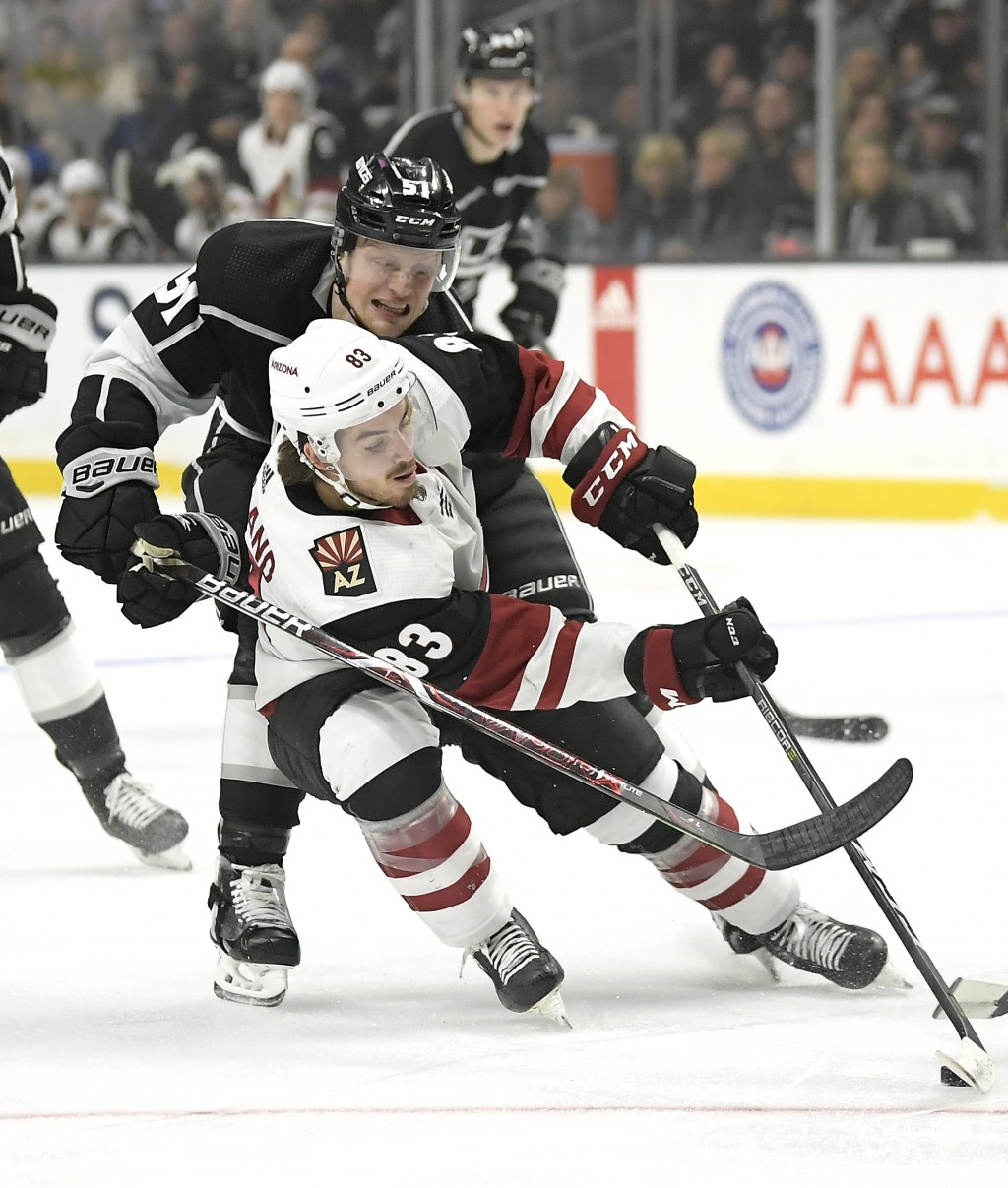 Los Angeles Kings left wing Austin Wagner, top, reaches for the puck in front of Arizona Coyotes right wing Conor Garland during the first period of a...