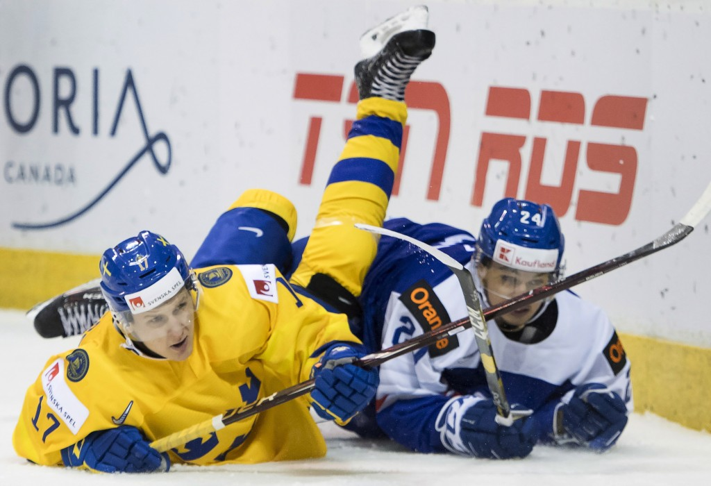 Sweden's Filip Sveningsson (17) fights for control of the puck with Slovakia's Jozef Balaz (24) during the first period of a world junior hockey champ