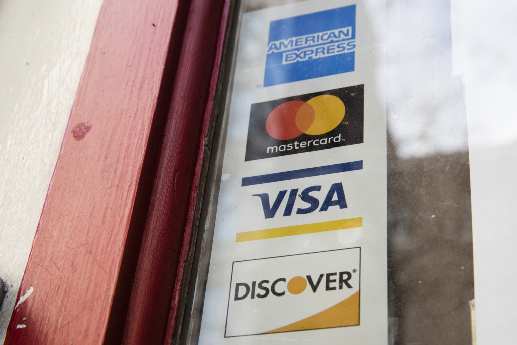 FILE - This Nov. 29, 2018, file photo shows are credit card logos posted on a store's door in Philadelphia. Simplify your taxes and maximize your inco