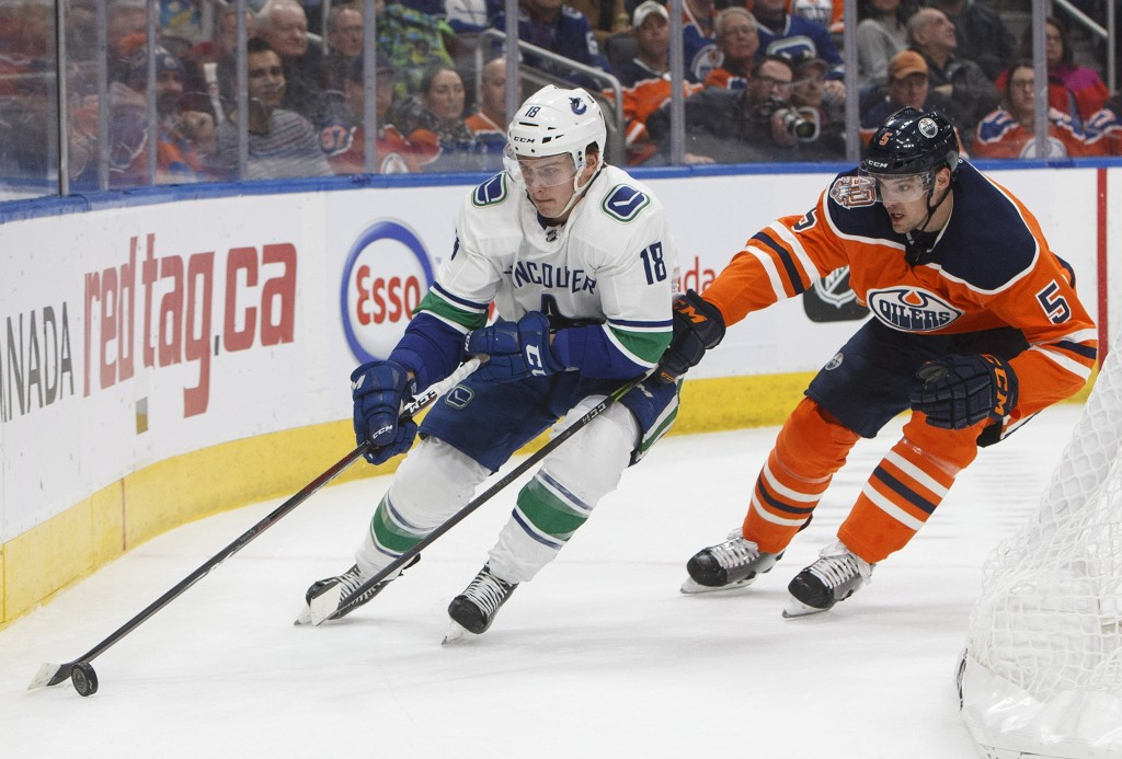 Vancouver Canucks' Jake Virtanen (18) is chased by Edmonton Oilers' Kevin Gravel (5) during the first period of an NHL hockey game Thursday, Dec. 27, ...