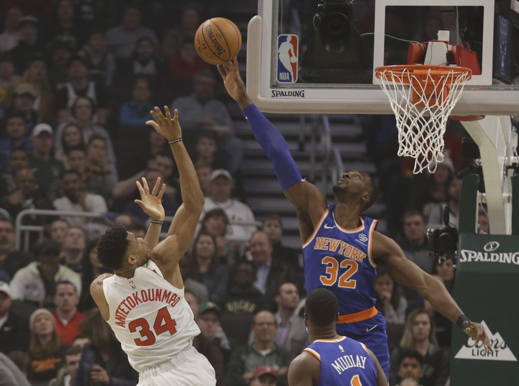 Milwaukee Bucks' Giannis Antetokounmpo (34) has his shot blocked by New York Knicks' Noah Vonieh (32) during the first half of an NBA basketball game ...