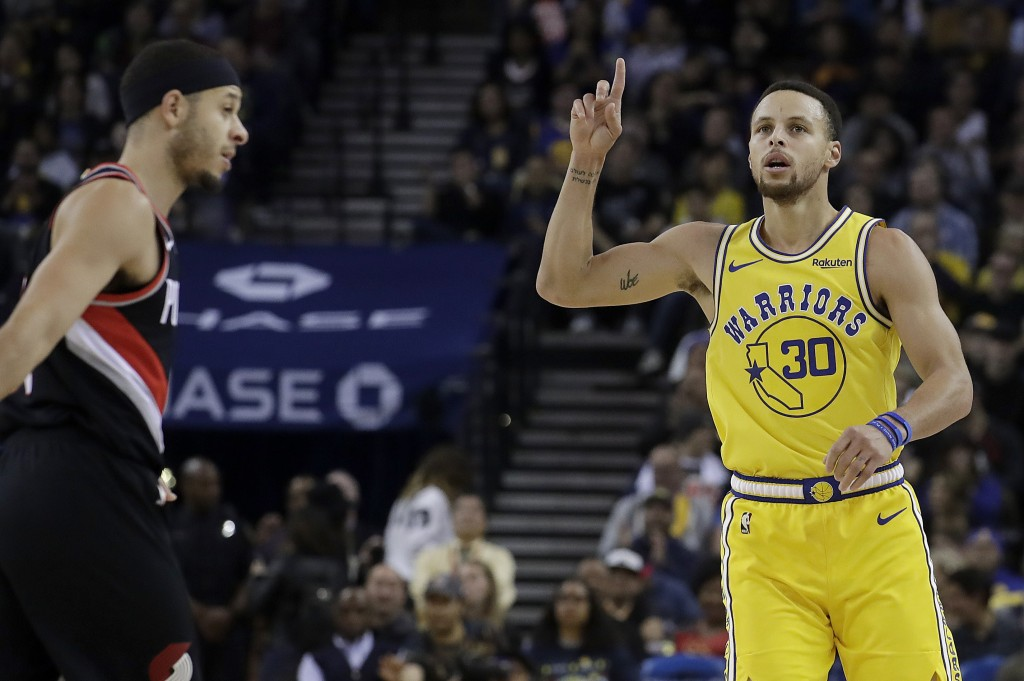Golden State Warriors guard Stephen Curry (30) celebrates after scoring, next to his brother, Portland Trail Blazers guard Seth Curry, during the firs...