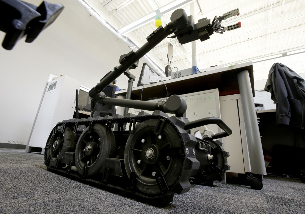 In this Aug. 28, 2018 photo a Centaur robot rests on a carpeted floor between desks at Endeavor Robotics in Chelmsford, Mass. The Army is looking for