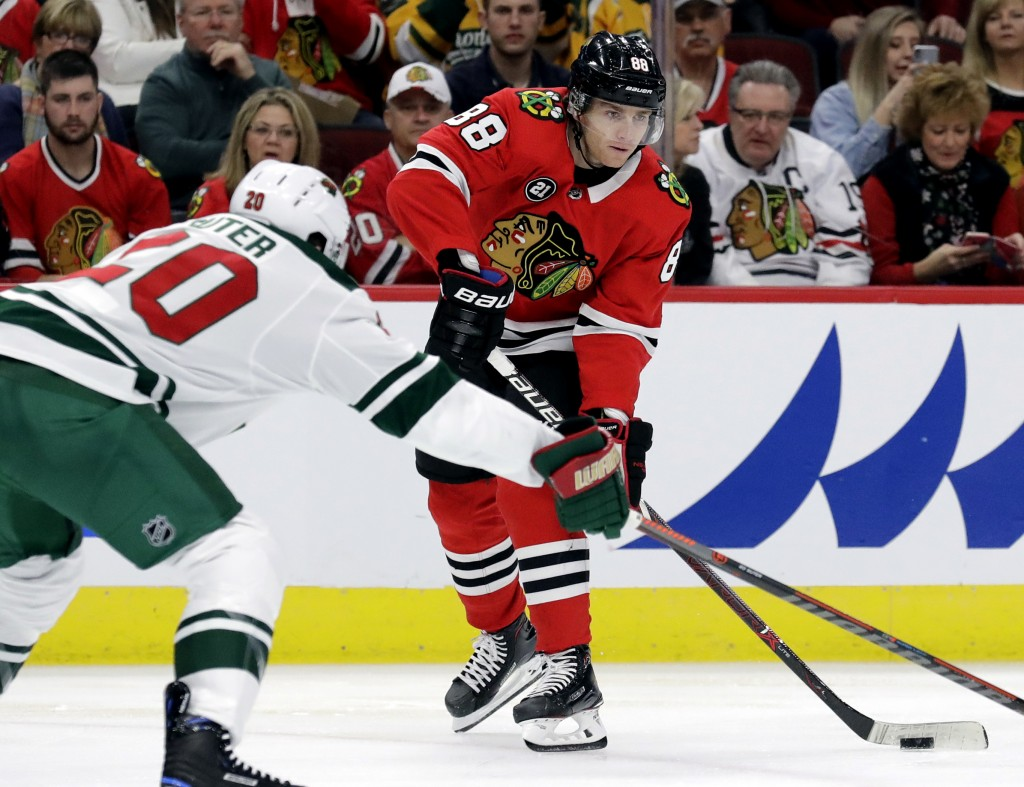 Chicago Blackhawks right wing Patrick Kane, right, looks to pass against Minnesota Wild defenseman Ryan Suter during the first period of an NHL hockey...