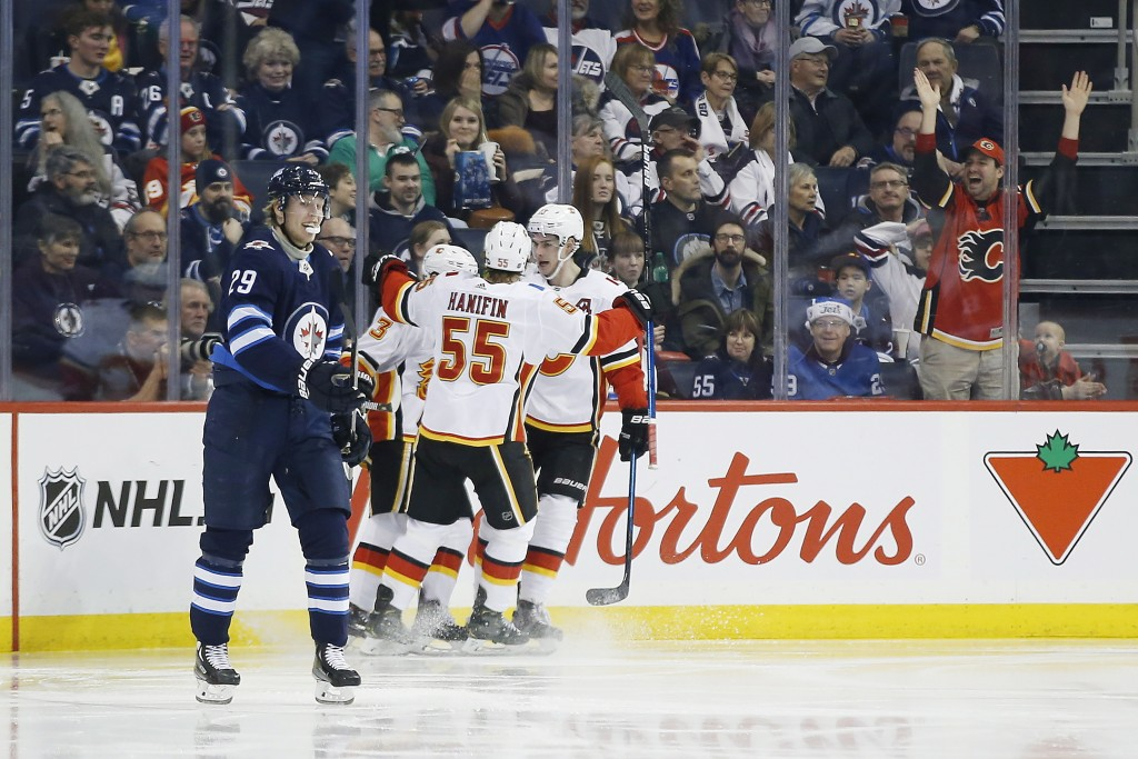 Calgary Flames' Noah Hanifin (55), Johnny Gaudreau (13) and Sean Monahan (23) celebrate Gaudreau's goal that went off the stick of Winnipeg Jets right...