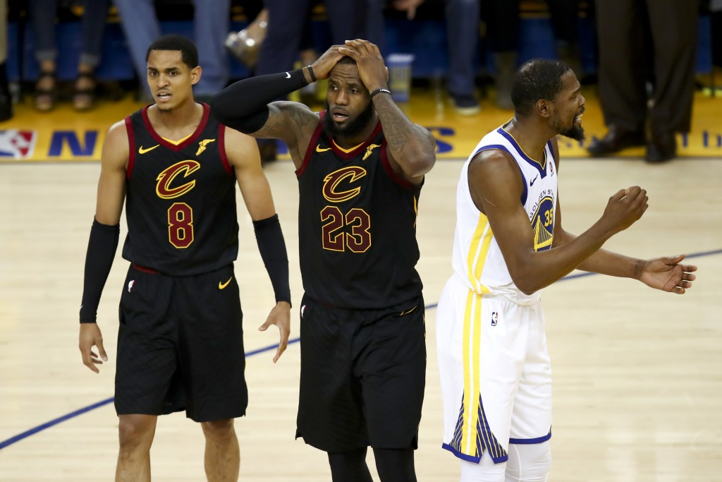 FILE - In this May 31, 2018, file photo, Cleveland Cavaliers forward LeBron James (23) reacts between guard Jordan Clarkson (8) and Golden State Warri...