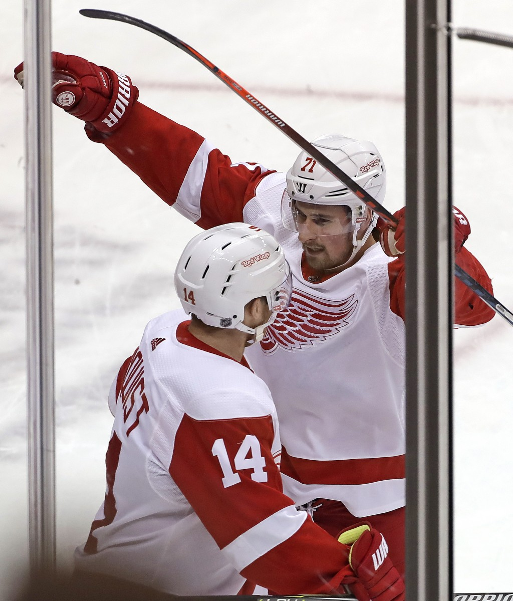 Detroit Red Wings' Dylan Larkin (71) celebrates his goal with Gustav Nyquist (14) during the first period of an NHL hockey game against the Pittsburgh