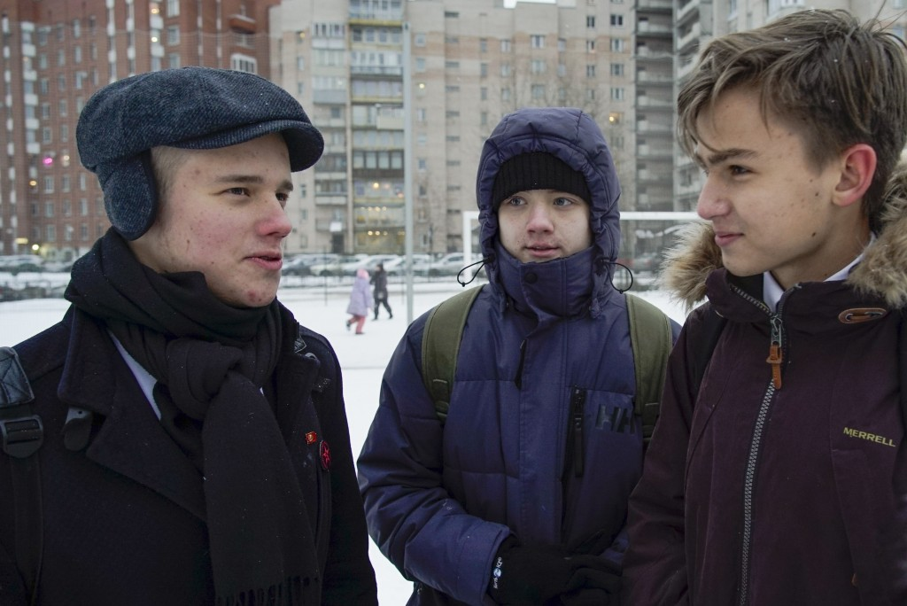 In this photo taken on Wednesday, Dec. 19, 2018, Leonid Shaidurov, left, Maxim Dautov, center, and Andrei Vorsin talk, outside their school in St. Pet...