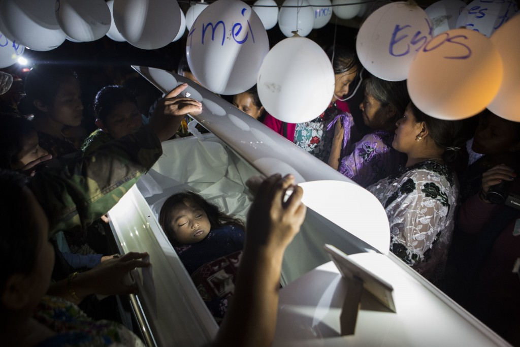 Family members pay their final respects to 7-year-old Jakelin Caal Maquin during a memorial service in her grandparent's home in San Antonio Secortez,...