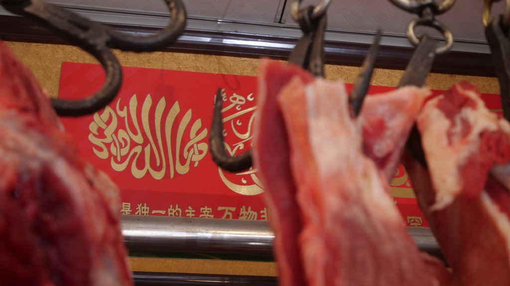 "In this Dec. 7, 2018, photo, an Arabic inscription reading ""there is no god but God"" is hung in a butcher shop in the Islamic neighborhood of Niujie i"