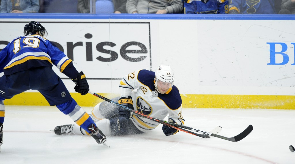 Buffalo Sabres' Johan Larsson (22), of Sweden, reaches for the puck with St. Louis Blues' Jay Bouwmeester (19) during the second period of an NHL hock