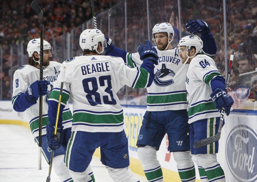 Vancouver Canucks' Chris Tanev (8), Jay Beagle (83), Alexander Edler and Tyler Motte (64) celebrate a goal against the Edmonton Oilers during the firs...