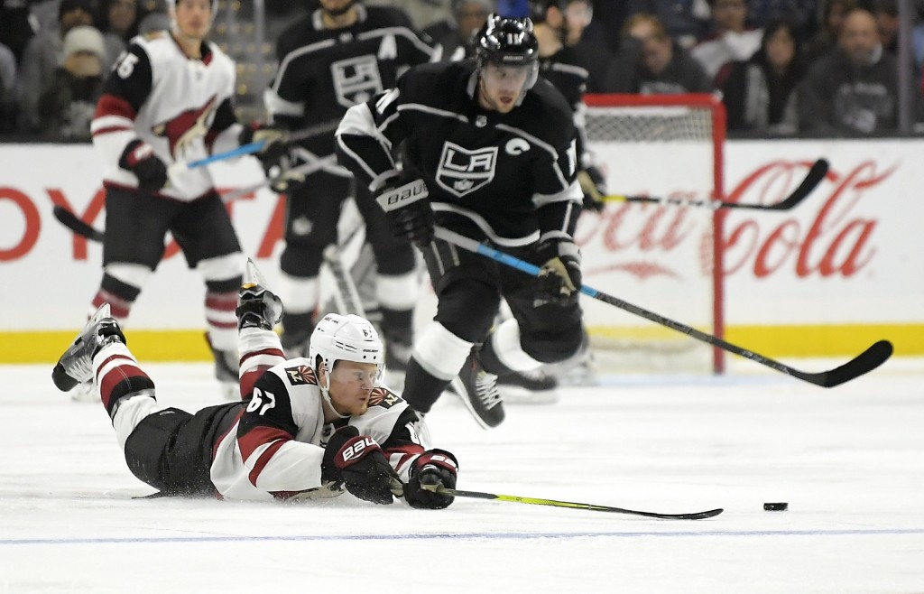 Arizona Coyotes left wing Lawson Crouse, left, dives for the puck as Los Angeles Kings center Anze Kopitar, of Slovenia, skates behind him during the ...