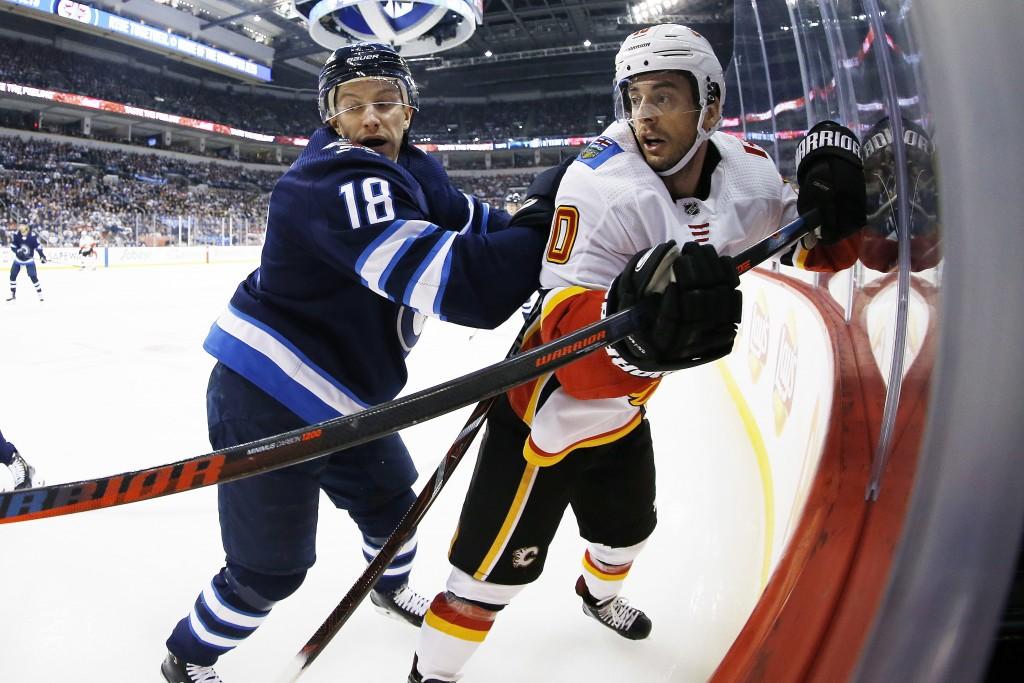 Winnipeg Jets' Bryan Little (18) checks Calgary Flames' Derek Ryan (10) during first-period NHL hockey game action in Winnipeg, Manitoba, Thursday, De...