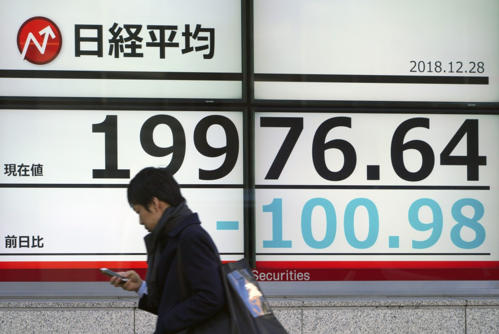 A man walks past an electronic stock board showing Japan's Nikkei 225 index at a securities firm in Tokyo Friday, Dec. 28, 2018. Most Asian stock mark...