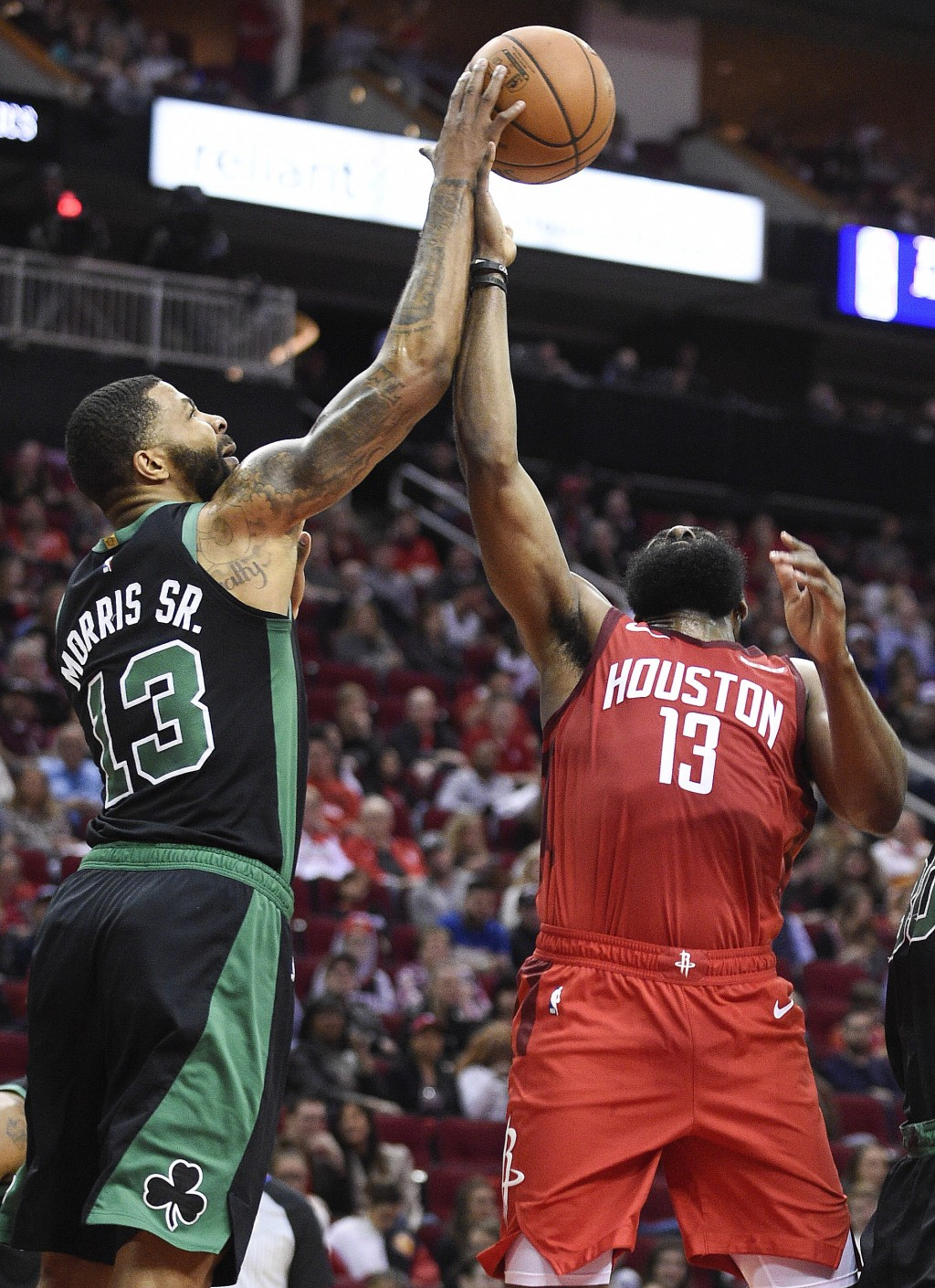 Boston Celtics forward Marcus Morris, left, blocks the shot of Houston Rockets guard James Harden during the first half of an NBA basketball game, Thu...