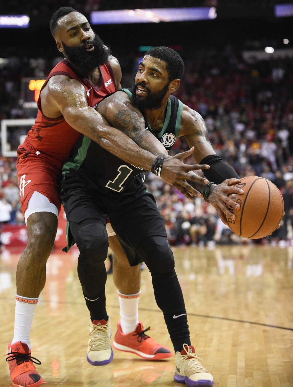 Boston Celtics guard Kyrie Irving, right, looks to pass as Houston Rockets guard James Harden defends during the second half of an NBA basketball game...