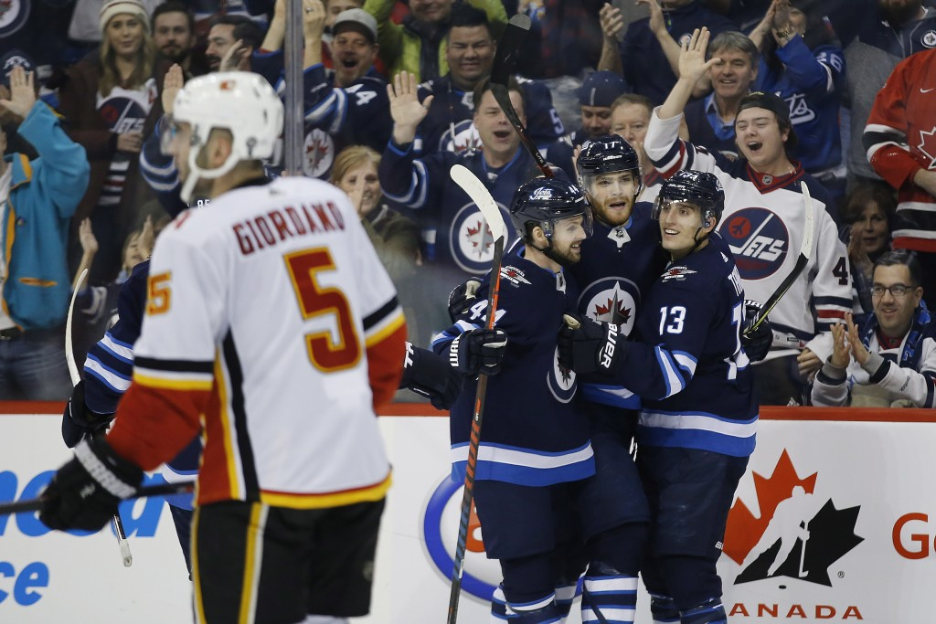 Winnipeg Jets' Josh Morrissey (44), Adam Lowry (17) and Brandon Tanev (13) celebrate Lowry's goal against the Calgary Flames during second-period NHL ...
